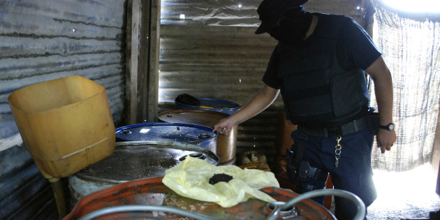 Policeman inspects barrels containing stolen diesel fuel, stored in a tyre repair shop, during an operation in the municipality of Apodaca